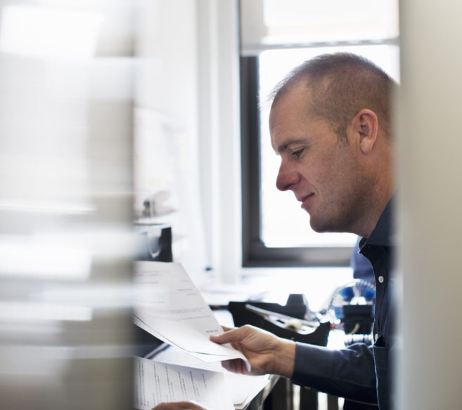 A man working in an office, reading paperwork.